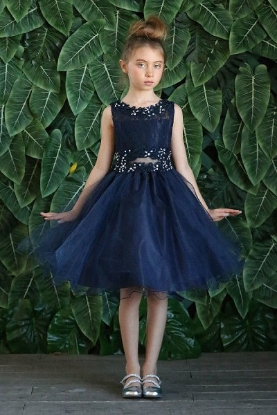 Young girl wearing a Calla Collection Dress D791 in Navy. Lace and tulle dress with illusion two piece middle, crystal embellishment on the bodice and a full tulle skirt with a ribbon tie at the back from Silhouette London, Girls party dress specialists in London