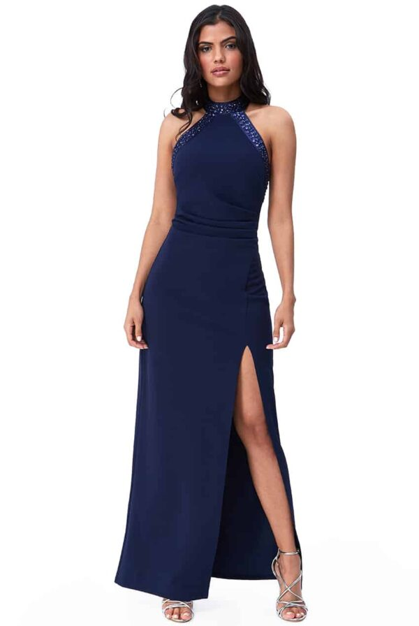 Young woman wearing a Diamante Halter Neck Maxi Dress in Navy. Backless crepe dress with a stunning diamante trim at the neckline and bodice edge from Prom Dress Boutique Silhouette London