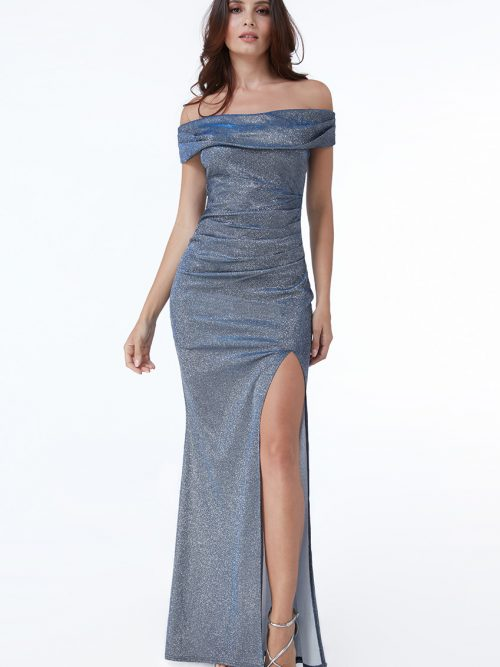 Young woman wearing a Bardot Shimmer Maxi Dress in Steel Blue. All over shimmer in a fabulous steel blue makes this bardot style maxi dress with ruched detailing and a split skirt from Prom Dress Boutique Silhouette London