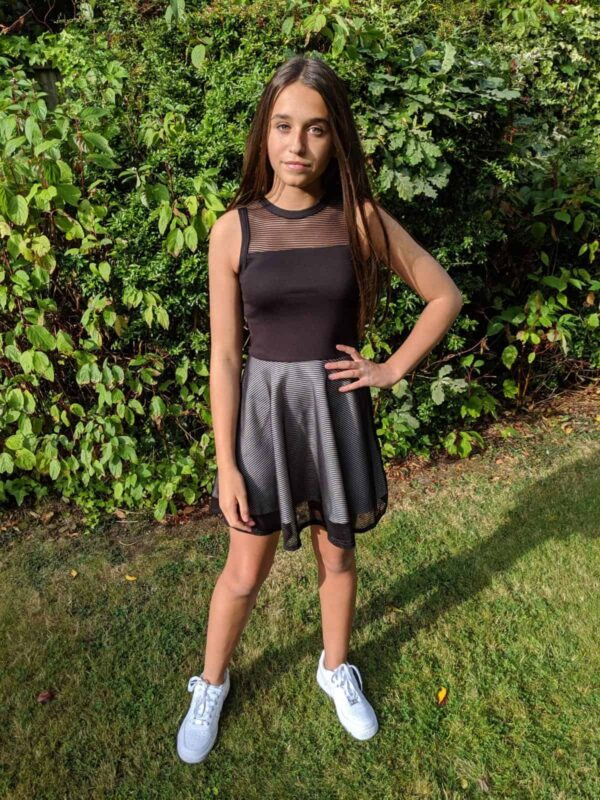 teenage girl wearing a Sally Miller Eden Dress. Fabulous mesh and jersey dress - jersey bodice with skater skirt with mesh overlay from Silhouette London, Girls party dress specialists in London