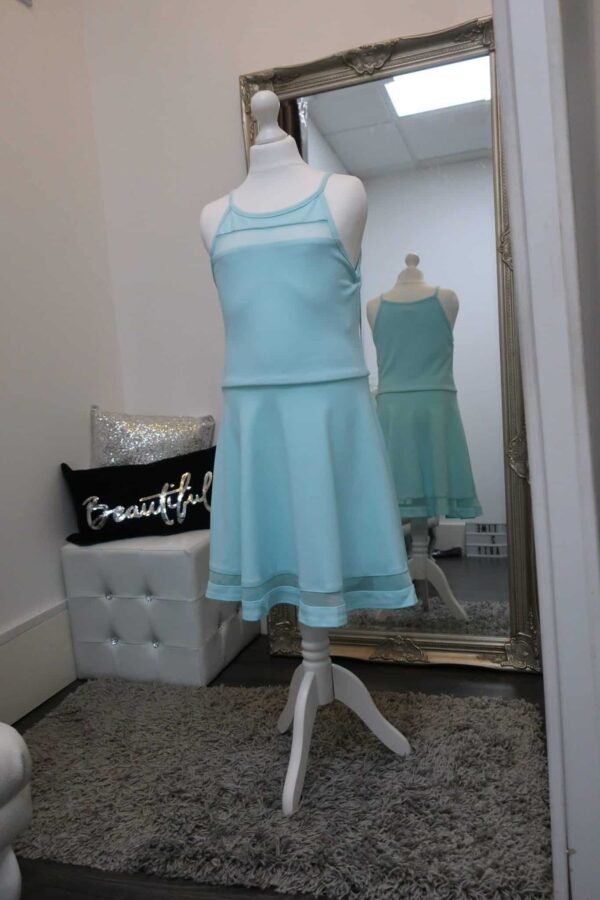 Sally Miller Tiffany Dress in Aqua. Jersey Skater Dress with mesh inserts at the neckline and on the skirt from Silhouette London, Girls party dress specialists in London