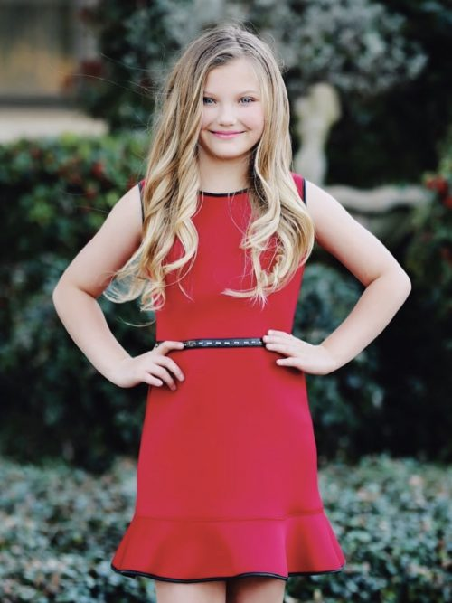 Young girl wearing a Dolls and Divas Couture Alana Dress in red. Wonderful red scuba dress with embellished waistband and straight fluted skirt. Ribbon edged bodice and neckline from Silhouette London, Girls party dress specialists in London