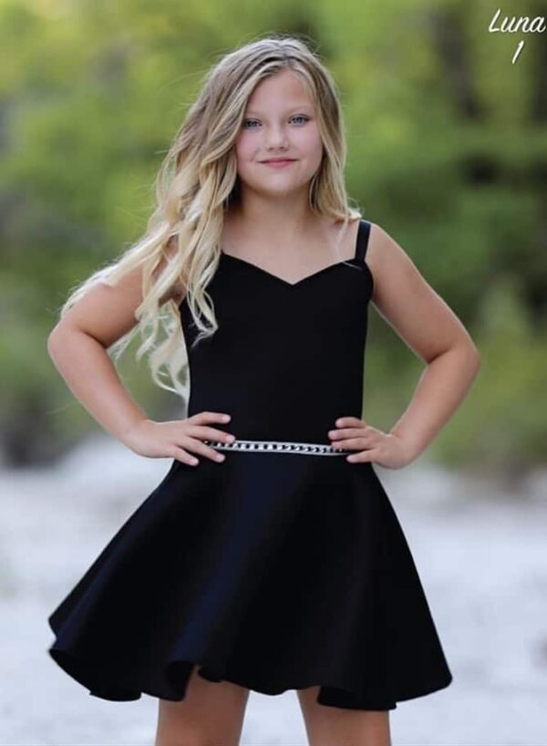 Blonde girl wearing a Dolls and Divas Couture Luna 1 Dress in Black, Scuba skater dress with embellished waistband from Silhouette Londone, Girls Party Dress Specialist in London.