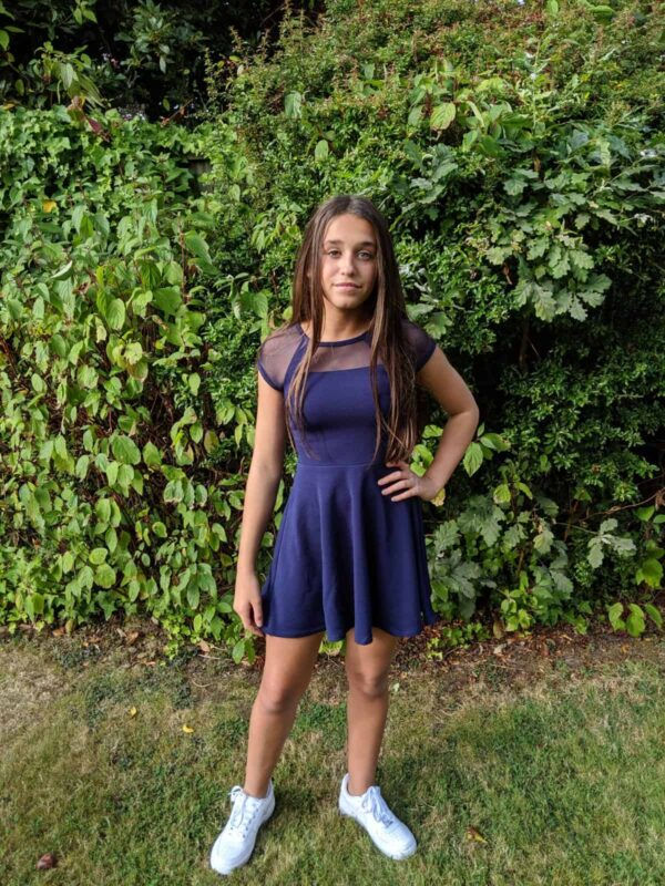 Teenage girl wearing a Sally Miller Shea Dress in Navy. Stunning cap sleeve textured jersey skater dress with mesh detail at the neckline and sleeve from Silhouette London, Girls party dress specialists in London