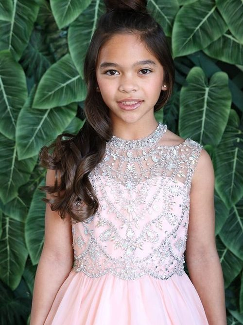 Young girl wearing a Calla Collection Dress TY010 in Blush Pink. Fabulous crystal embellishment adorns this stunning cold shoulder bodice with a beautiful chiffon skirt from Silhouette London, Girls party dress specialists in London