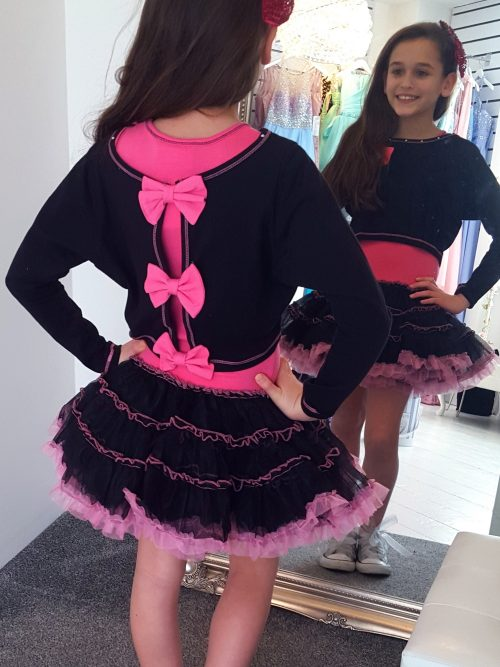 Young girl wearing Ooh la la Couture fabulous jersey crop top with gorgeous hot pink stitching and hot pink bows on the back over a jersey bodice and black & hot pink tutu skirt from a Girls Party Dress Specialist Boutique