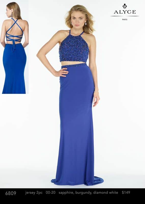 Young blonge model wearing a Alyce Paris Two Piece Dress Style 6809 Sapphire. Jersey two piece with a slim skirt, embroidered at the waist. Embellished halter top with an open back from Prom Dress Boutique Silhouette London.