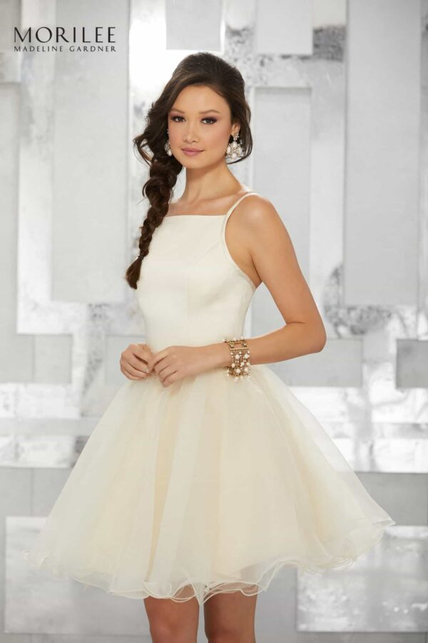 Brunette teenage girl wearing a Mori Lee Dress Style 9459. Satin Halter neck bodice with full tulle skirt from Silhouette London, Girls party dress specialists in London.