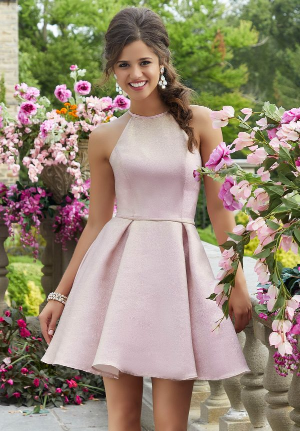 Young Woman wearing Mori Lee Dress Style 9538 Halter Neck Bodice with box pleated Skirt and Strappy Back in Pink Shimmer from Batmitzvah Dress Specialist Boutiqe Silhouette London.