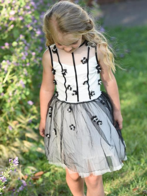 Small young girl wearing a white, grey and black Ooh La La Couture Adele Dress, from Children's fashion specialist Silhouette London.