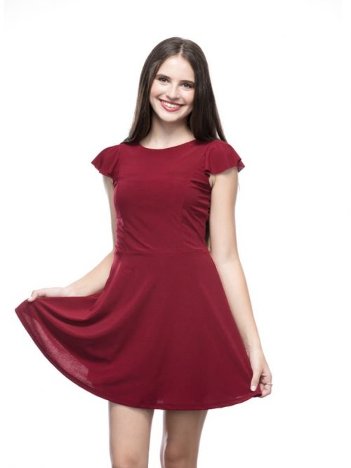 Young girl wearing a Un Deux Trois Flutter Dress in Burgundy. Silky jersey skater dress with fluted cap sleeve and fluted V Back from Silhouette London, Girls party dress specialists in London