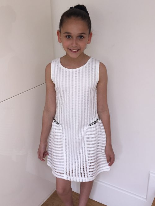 Young girl wearing Ivory skater style dress with side chain detail in ladder mesh like fabric from Party Dress Boutique, Silhouette London