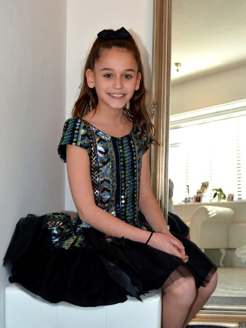 Young Girl sitting wearing Dolls and Divas Chloe Dress in Aztec Design sequins and black tulle Skirt from Girls Party Fashion Boutique Silhouette London