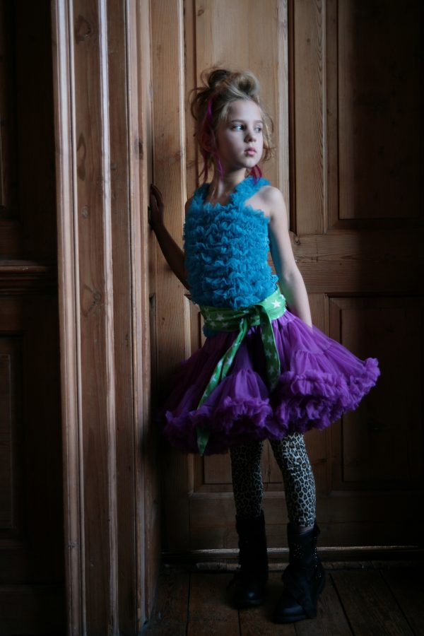 Young Girl wearing an Angels Face Ruffle Top in Peacock Blue from Silhouette London a Girls Party Boutique in Greater London