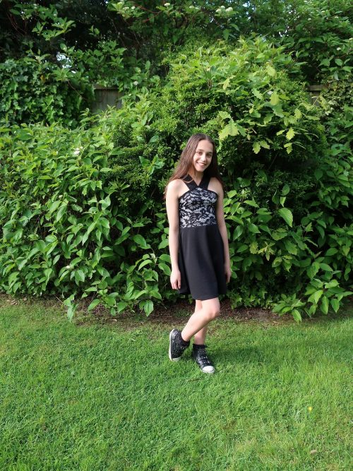Young Girl wearing Lace and Jersey V Strap Skater dress in Black/Nude from Silhouette London, Girls Prom and Party Dress Boutique in London