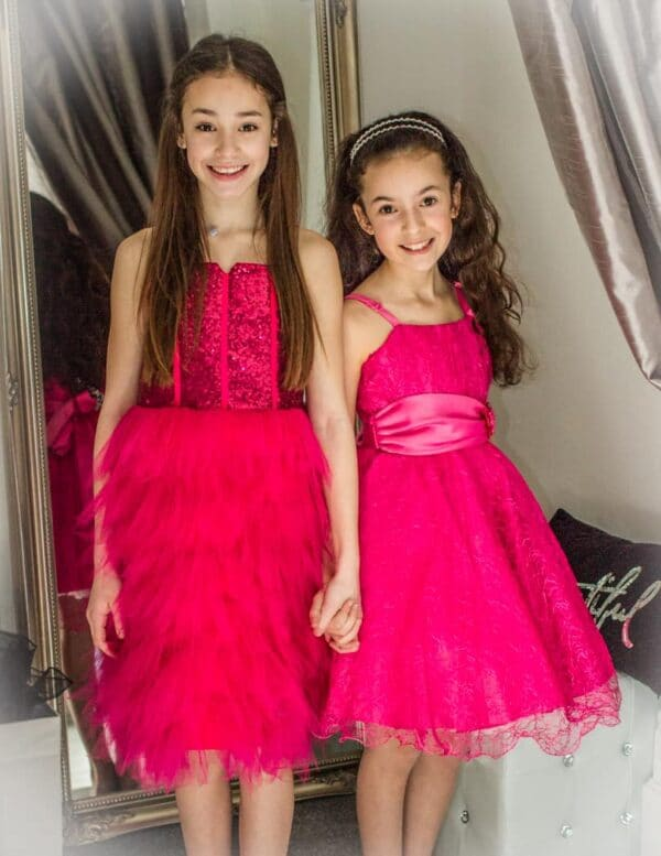 Young girls wearing a Sequin & Tulle Tiered Dress in Hot Pink with sequin bodice with tie up back and spaghetti straps from Silhouette London, Girls party dress specialists in London