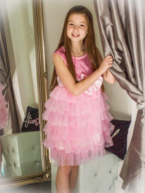 Young Girl wearing a Sequin & Tulle tiered Dress in Pink with a Hot Pink Satin Bow from Silhouette London, a Girls Party Dress Boutique in Greater London.
