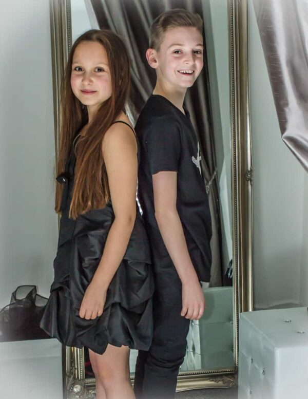 Young Girl wearing a Taffeta Dress with Pick Up Skirt in Black standing with young boy in black t shirt from Silhouette London a Party Fashion Boutique in Greater London