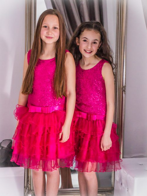 Young girls wearing Dolls and Divas Couture Amy Dress in Fuschia. Sequin bodice, satin bow waistband and tiered organza skirt from Silhouette London, Girls party dress specialists in London.