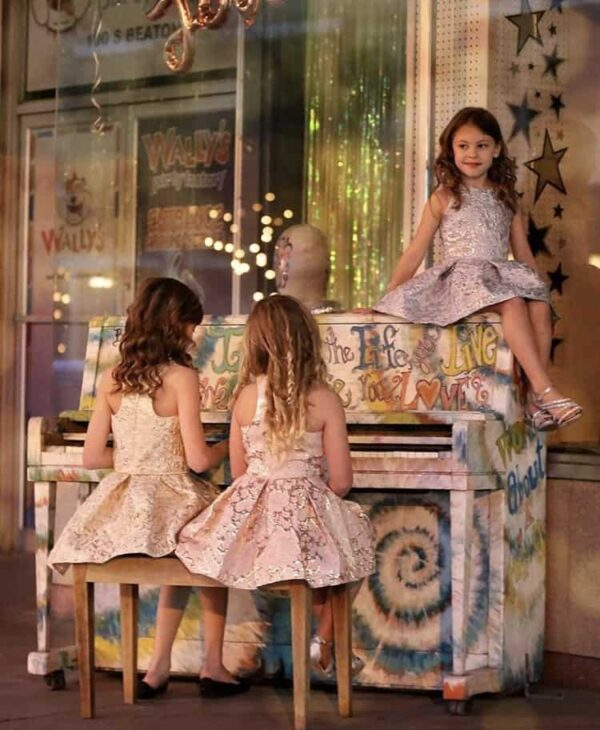 Three young Girls wearing Dolls and Divas Couture Jodi 2 Dress in fabulous gold shimmer brocade with racer back, bought from Silhouette London, a Girls Party Fashion Boutique in Harrow, Greater London