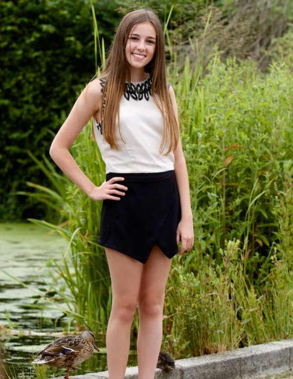 Teenage Girl wearing the TFNC Black Lewis Skort in black stretch crepe with the Ivory and Black embellished TFNC top from Occasion Wear Boutique Silhouette London
