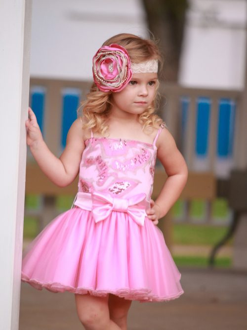 Little Girl wearing Dolls and Divas Couture Divas Party Dress Marly 1 with embellished bodice with spaghetti straps, matching satin bow and full tulle skirt in Pink from Girls Party Dress Boutique Silhouette London