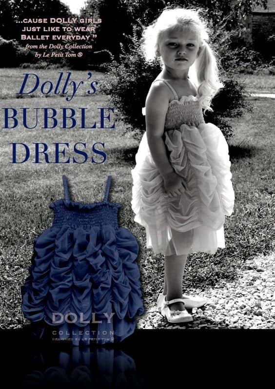 Young girl wearing a Dolly Le Petit Tom Bubble dress in Navy from Silhouette London, Girls party dress specialists in London.