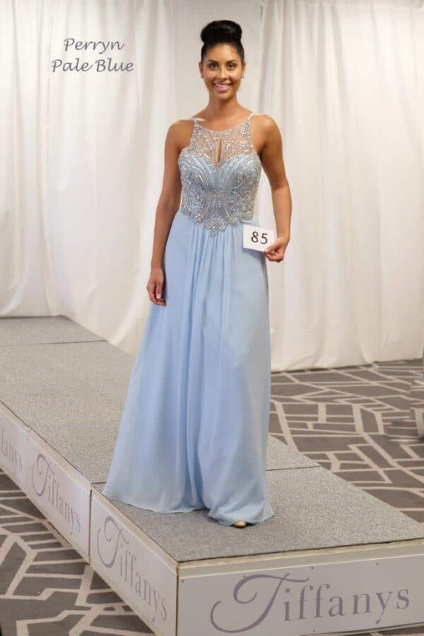 Brunette women wearing a Tiffany Illusion Prom Perryn Dress in Light Blue. Beautiful Crystal embellishment adorn this beautiful chiffon dress with flowing skirt and strappy open back from Prom Dress Boutique Silhouette London.
