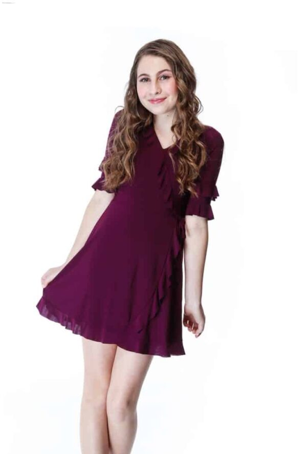 Teen Girl wearing an Un Deux Trois Jersey wrap dress with 3/4 fluted sleeves in Plum from Silhouette London, a Girls Party Dress Boutique in London