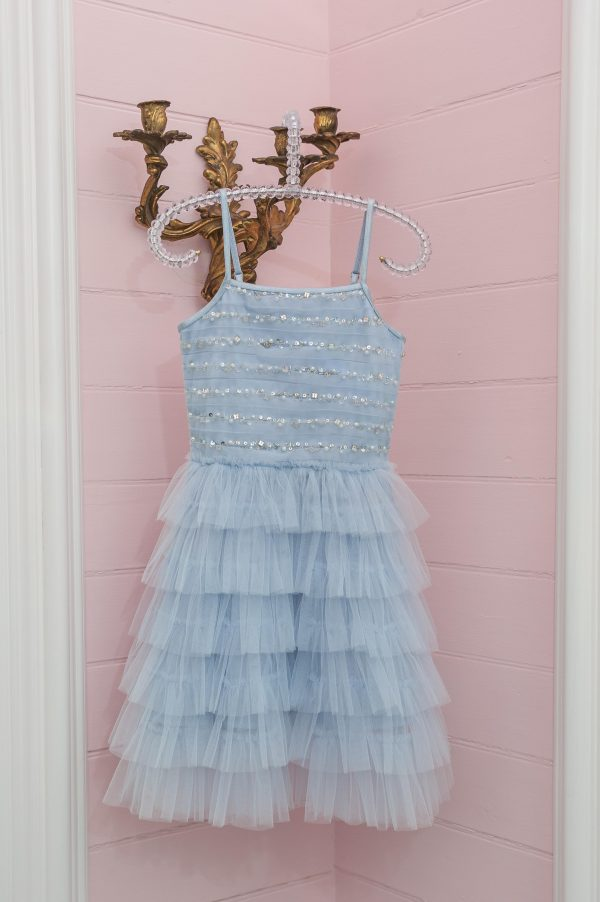 A picture of a Ooh La La Couture Rain Dress in blue, the perfect little girls party dress, hanging from a candleholder at Children's fashion specialist Silhouette London.