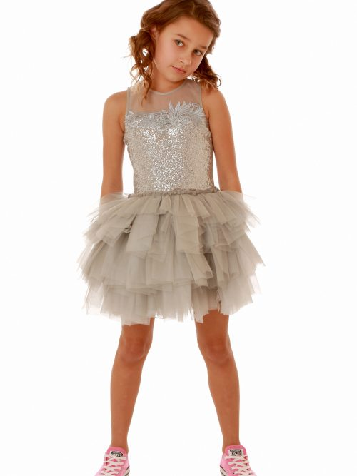 Young girl wears Ooh La La Couture'sOoh la la Couture's Sequin Sheer Shoulder Dress in Silver with tiered tulle skirt from Girls Party Dress Boutique, Silhouette London