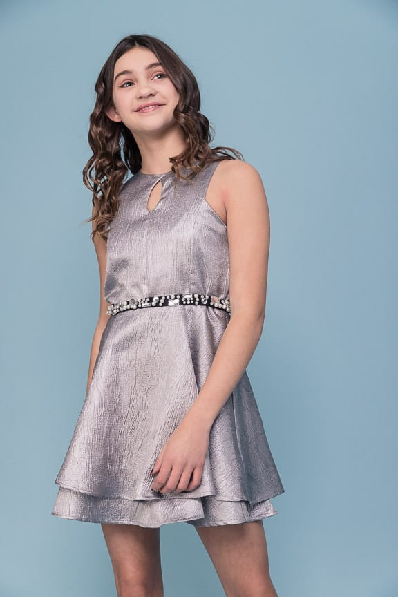 Teenage Girl wearing Un Deux Trois Metallic Silver Halter Neck Tiered Jacquard Dress from Silhouette London, Girls Party Fashion Boutique in Harrow, Greater London