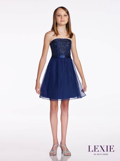 Young girl wearing a Mon Cheri Lexie Dress Style TW11673 in Navy. Strapless chiffon over satin above-the-knee A-line dress, hand-beaded lace overlay bodice, satin waistband, chiffon overlay skirt from Prom Dress Boutique Silhouette London.