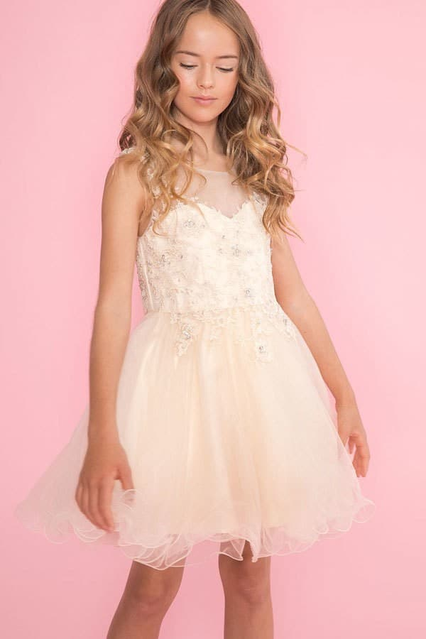 Young girl wearing a Calla Collection Dress TY002 in Champagne. Stunning lace and tulle dress with illusion neckline and full tulle skirt with scalloped edge from Silhouette London, Girls party dress specialists in London.