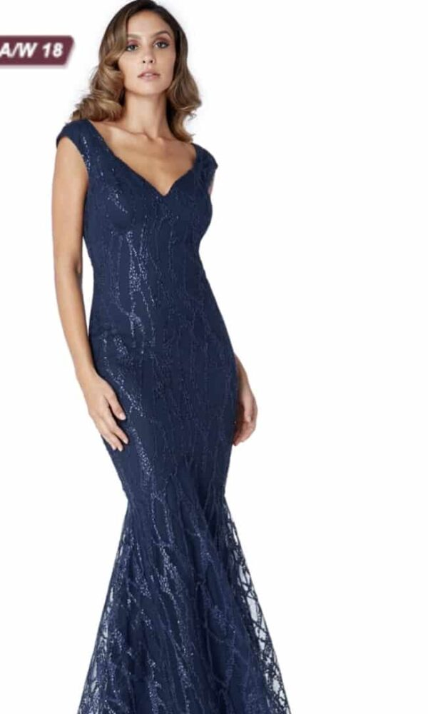 Young women wearing a Sweetheart Sequin Mermaid Dress in Navy. Sequin Mermaid Dress with a sweetheart neckline and cap sleeve and open back with shimmering sequin detail throughout from Prom Dress Boutique Silhouette London