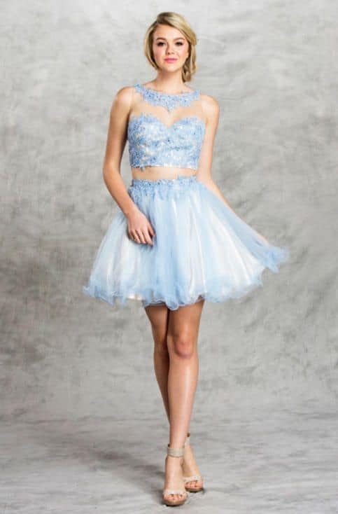 Blonde teenager wearing a Aspeed Design Dress Style S1482 in Periwinkle Blue. lace and tulle two piece with full tulle skirt with scalloped edge and fabulous lace and tulle illusion neckline on the top from Silhouette London, Girls party dress specialists in London.