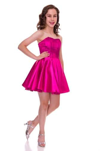 Young girl wearing a Un Deux Trois Sequin and Satin Dress in magenta. strapless sequin bodice tops a gorgeous satin skirt from Silhouette London, Girls party dress specialists in London.