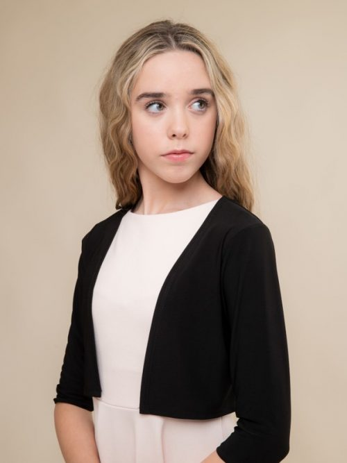 Blonde teenage girl wearing an Un Deux Trois Black Jersey Bolero from Silhouette London, Dress Boutique Specialist in London.