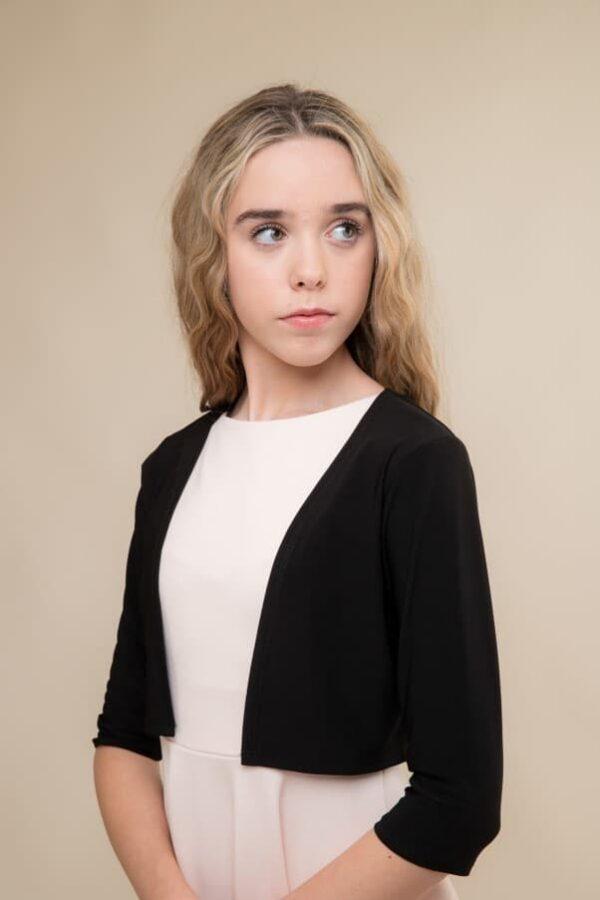 Blonde teenage girl wearing an Un Deux Trois Black Jersey Bolero from Silhouette London, Dress Boutique Specialist in London.