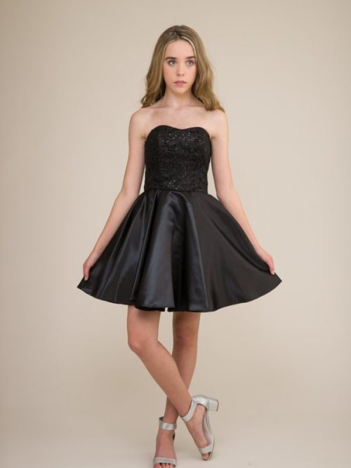 A teenage girl wearing a black Un Deux Trois Sequin & Satin Dress, from Prom Dress boutique Silhouette London.