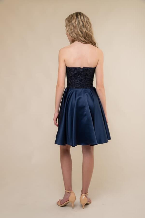 A picture of a Blonde teenage girl, facing away from the camera, wearing an Un Deux Trois Glitter Lace Dress prom dress from Boutique Silhouette London