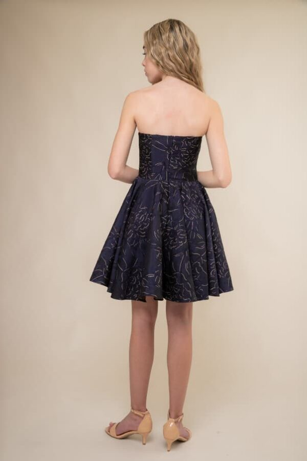 A picture of a teenage girl, facing away from the camera, wearing an Un Deux Trois Navy Jacquard Strapless Short Dress, the perfect Prom Dress, from Silhouette London.