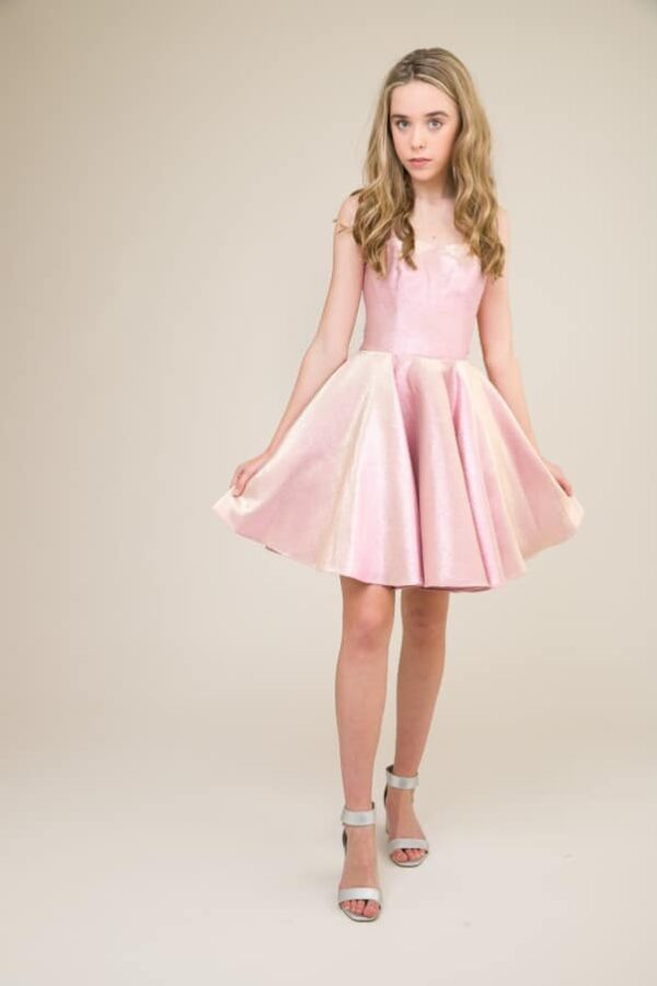 A picture of a teenage girl wearing Un Deux Trois Pink Shimmer Dress, the perfect Prom Dress, from Silhouette London.