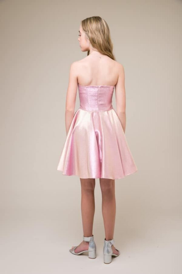 A picture of a teenage girl, facing away from the camera, wearing Un Deux Trois Pink Shimmer Dress, the perfect Bat Mitzvah dress, from Silhouette London.