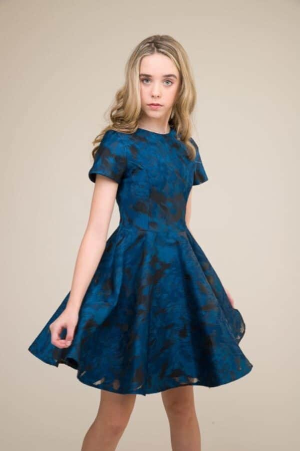 Blonde teenage girl wearing an Un Deux Trois Short Sleeve Blue Jacquard Dress, from Silhouette London, Prom dress specialists in London.