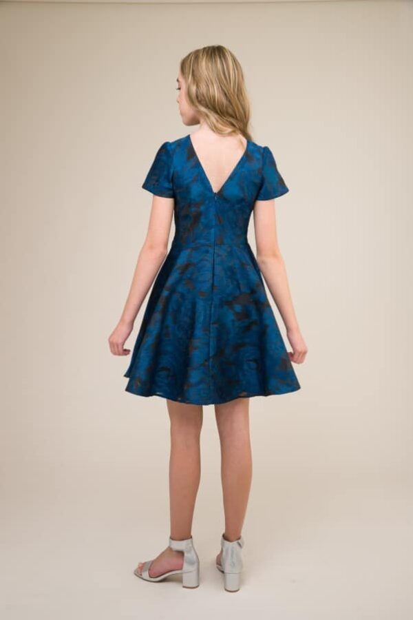 A picture of a Blonde teenage girl, facing away from the camera, wearing an Un Deux Trois Short Sleeve Blue Jacquard Dress, from Silhouette London, Prom dress specialists in London.