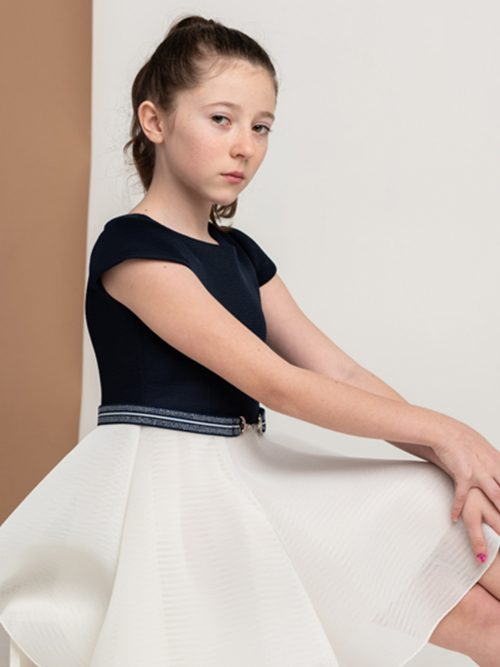 Young girl sitting down wearing Zoe Ltd Emersyn Dress in Navy and Cream from Silhouette London a Girls Party Dress Boutique in London