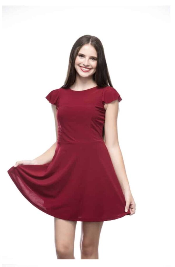 Young girl wearing a soft jersey burgundy Un Deux Trois Flutter Dress from Silhouette London a Girls Party Dress Boutique in Greater London.
