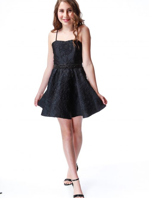 Young Girl wearing Un Dux Trois black All over Jacquard dress with spaghetti straps and skater skirt available at Silhouette London a Tween Party Dress Boutique in Greater London.