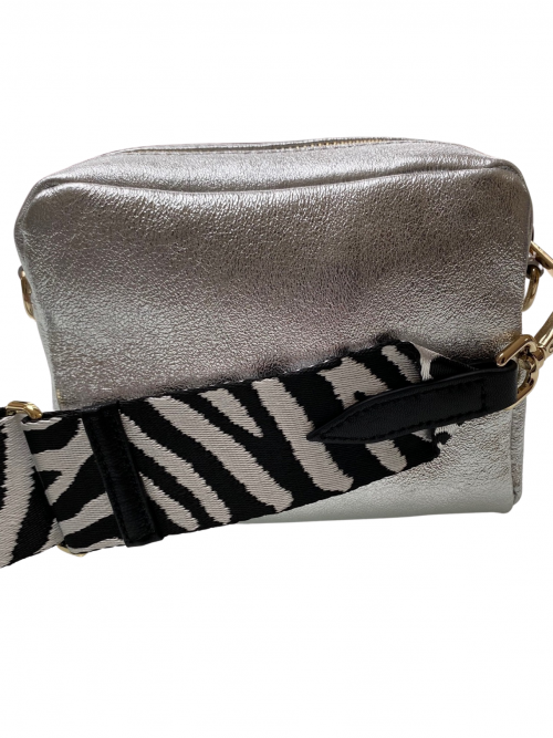 Silver leather crossbody bag with zebra adjustable strap on a white background available from silhouette london, a teen fashion boutique in Greater London